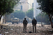 Egyptian military soldiers stand idle down a side-street,  just a few dozen meters from ongoing clashes between protesters and Egyptian riot police November 22, 2011 near Tahrir square in central Cairo, Egypt. Thousands of protestors demanding the military cede power to a civilian government authority clashed with Egyptian security forces for a fourth straight day in Cairo, with hundreds injured and at least 29 protestors killed so far.  (Photo by Scott Nelson)