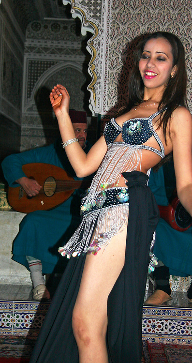 North Africa, Morocco, Marrakesh. A Belly Dancer performs for diners at a traditional Moroccan restaurant.