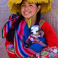 """CUSCO , PERU - MAY 28 : Unidentified Peruvian girl in traditional colorful clothes holding a lamb in here arms in the """" Unesco world heritage"""" city """"Cusco"""" on May 28 2011"""