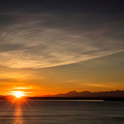 Thin cirrus clouds fill the sky over the Olympic Mountains as the sun sets over Puget Sound in this view from Richmond Beach, Washington.