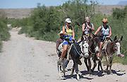 Karla Kahn, left, Callie Fields, center, and Callie Jacks, right, ride donkeys into Boquillas del Carmen from Big Bend National Park.