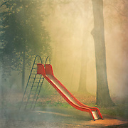 Playgroung shrouded in fog.<br /> You can license this through Gettyimages:<br /> http://www.gettyimages.de/detail/foto/red-slide-on-foggy-morning-lizenzfreies-bild/120627290?esource=en-us_flickr_photo
