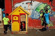 FEIRA DA KANTUTA - Crianças brincam em casinha de bonecas enquanto jogadores bolivianos se preparam para partida de futebol em quadra da praça Kantuka, no bairro Canindé, em São Paulo. 26/06/2016
