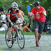 A spectator (RIGHT) encourages a cyclist as the rider travels up the steep hill of the Monkey Hill course during day two of The Wilmington Grand Prix Monkey Hill Time Trials Friday, May. 17, 2013 at Brandywine Park in Wilmington Del.