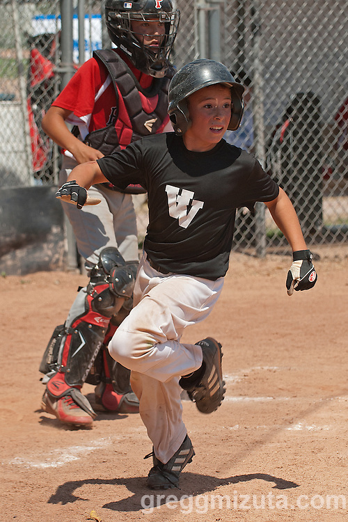 Jared Fulwyler scores during the Vale - Payette game at the Snake River Slug Fest Baseball Tournament at Mesa Recreation Park in Fruitland, Idaho on July 27, 2013.