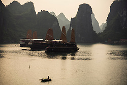 Junks moored in a quiet bay surrounded by limestones, Halong Bay, Vietnam, Southeast Asia