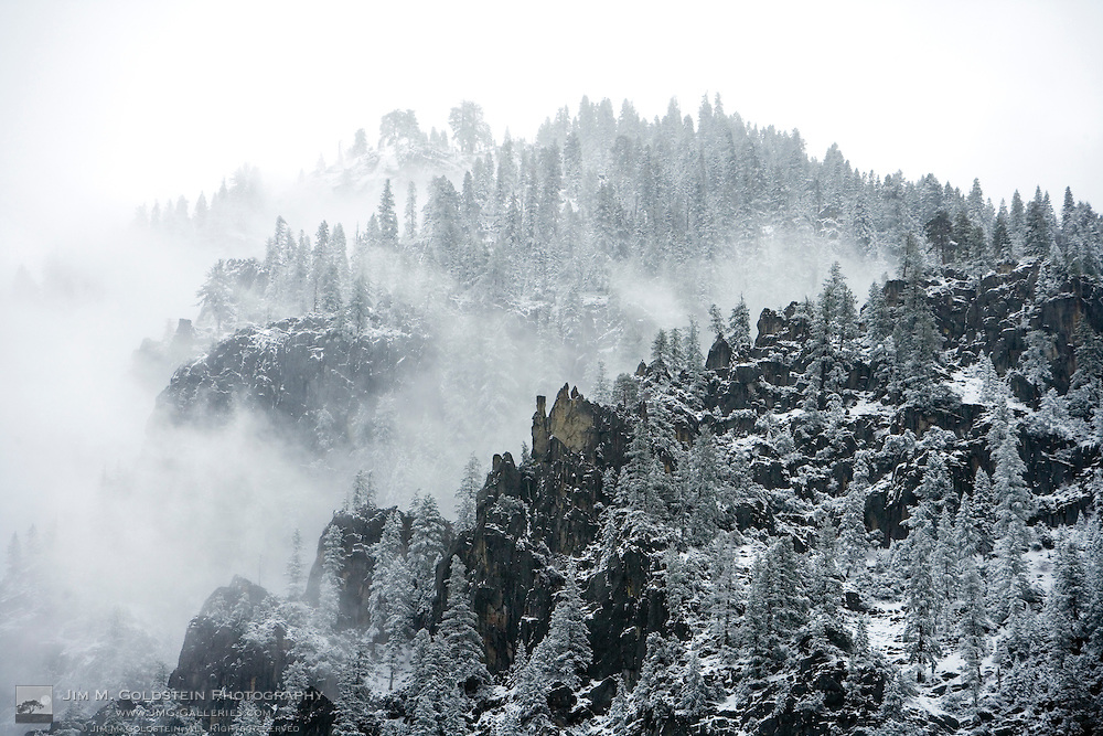 Clouds dissipate revealing snow covered granite cliffs and trees making up Yosemite valley's walls - Yosemite National Park, California
