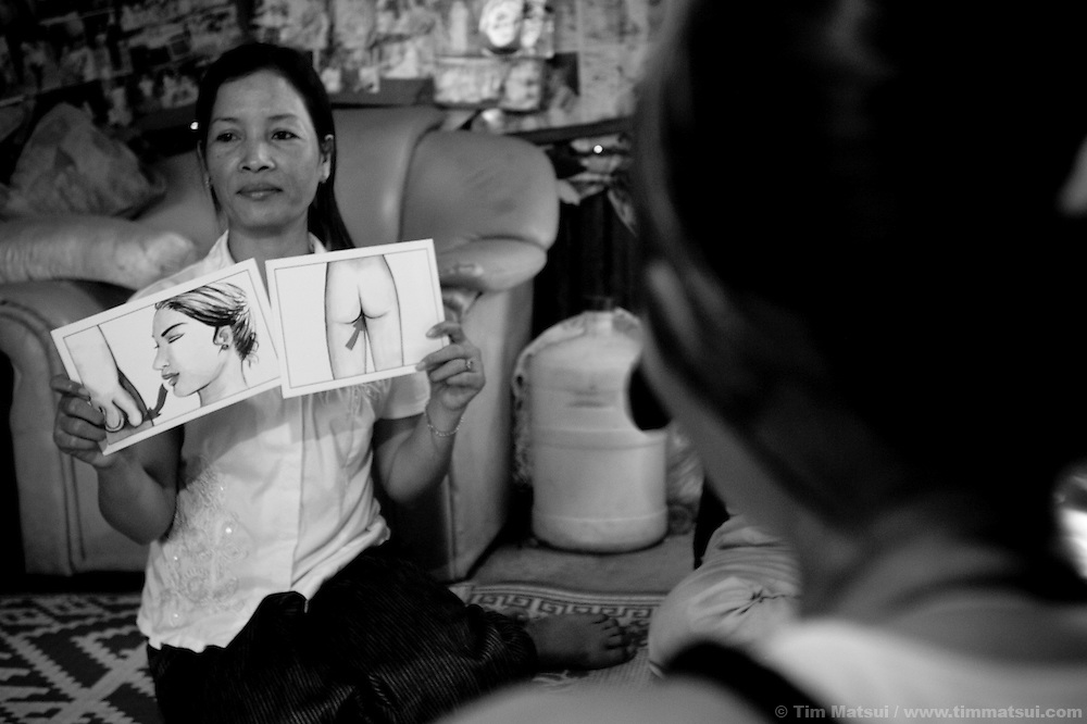"""Social worker team leader Ouch Vanna discusses HIV prevention with prostitutes in a slum where """"Acting for Women in Distressing Situations"""" (AFESIP) conducts outreach and provides services in Phnom Penh, Cambodia. The slum's permanent structure, a decaying four story building known simply as 'The Building', was built in the 1960's as transitional housing and now hosts a shantytown where many of the city's poor live, including many prostitutes, and is believed to have the highest rate of HIV infection in the city. AFESIP hands out free condoms, instructs prostitutes on HIV prevention, and conducts outreach in case the prostitutes need medical services, choose to leave their profession, or can report on cases of sex trafficking. AFESIP offers housing, education, training, and counseling for women who are victims of sex trafficking, worked as prostitutes, or are escaping domestic violence. Founded by Somaly Mam, who herself was once a prostitute and victim of trafficking and domestic abuse, AFESIP has three facilities in Cambodia and works with other NGO's to provide long term care for the women."""