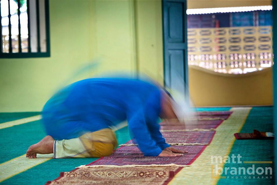A timed exposure of a  Muslim man praying.