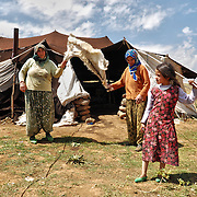 Shaking out a sheep pelt. Tents are improvised from materials such as sackcloth or donated by organizations like the Turkish Red Crescent.