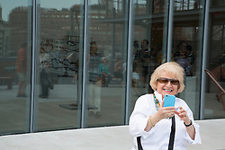 mature woman enjoying using an iphone at The Whitney Museum in New York City