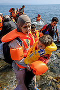 Mother and child that just arrived on a dinghy boat. <br /> Refugees arriving on beaches near Molyvos village in Lesvos island. Thousands of them come from Turkey, crossing the sea border on inflatable dinghy boats, on a dangerous trip that has claimed many lives. Local people or NGOs expect them and help them in some places but after their arrival, most of them have to walk to the nearest village where they can hope for a places on busses that can take them to the city of Mytilene where they can register and eventually board on a ferry to Athens. Many decide to walk the distance as the busses aren&rsquo;t enough to accommodate the large number of people that arrive daily.