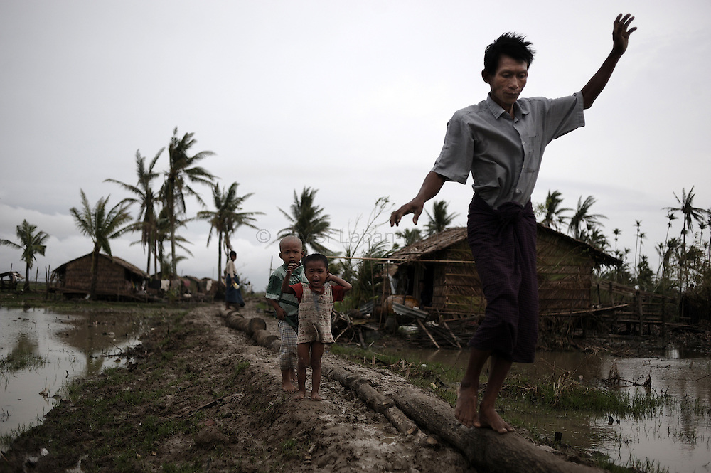 A man affected by cyclone Nargis balances on a piece of wood to avoid walking in the mud in Kaunt Chaung near Pyapon on May 20, 2008 in an isolated area only accessible by boat which received neither governement or foreign aid. UN Secretary General Ban Ki-moon said on May 21, 2008 he would meet Myanmar's reclusive junta leader during a high-profile trip to convince the country to accept a full-scale cyclone relief operation.