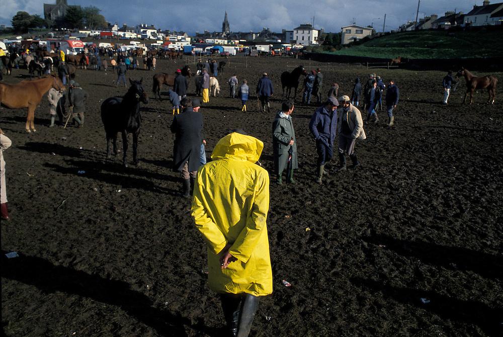 Ireland, County Galway, Ballinasloe, Man walks through muddy paddock at Ballinasloe Horse Fair on autumn afternoon