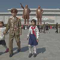 Pyongyang, North Korea, April 16 2012. A decorated military officer and his young grand-daughters walk near giant bronze statues of Kim il-Sung and Kim Jong-il at the Mansuadae Grand Monument. Citizens travelled en mass to the hilltop monument on the 100th anniversary of Kim il-Sung's birth to lay flowers and bow in front of the effigies of North Korea's late leaders.
