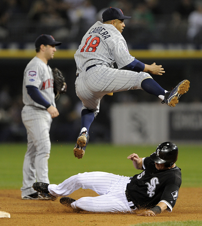CHICAGO - SEPTEMBER 23:  Orlando Cabrera #18 of the Minnesota Twins turns a double play over a sliding Jayson Nix #5 of the Chicago White Sox on September 23, 2009 at U.S. Cellular Field in Chicago, Illinois.  (Photo by Ron Vesely)