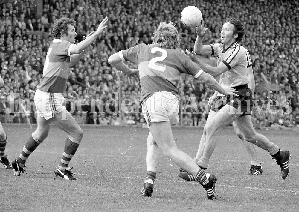 Dublin's Anton O'Toole palms the ball as Kerry's Mickey Sheehy and Jimmy Deenihan (2) come to tackle during the  Dublin v Kerry the winners 1979 All-Ireland final at Croke Park. (Part of the Independent Newspapers Ireland/NLI collection.)