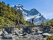 Trekkers cross a bridge in the French Valley (Valle Frances) beneath Paine Grande (2700 meters summit elevation) through a Nothofagus tree forest, in Torres Del Paine National Park, Chile, South America.