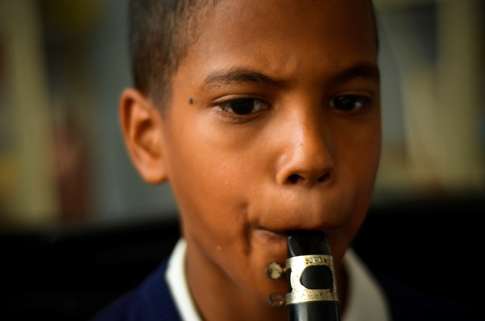 """Students in a beginners class practice playing their instruments in an after school program at the José Martí primary school in Sarría, a slum in Caracas, Venezuela. The school is a """"nucleo"""" for El Sistema, Venezuela's nationwide classical music educational program."""