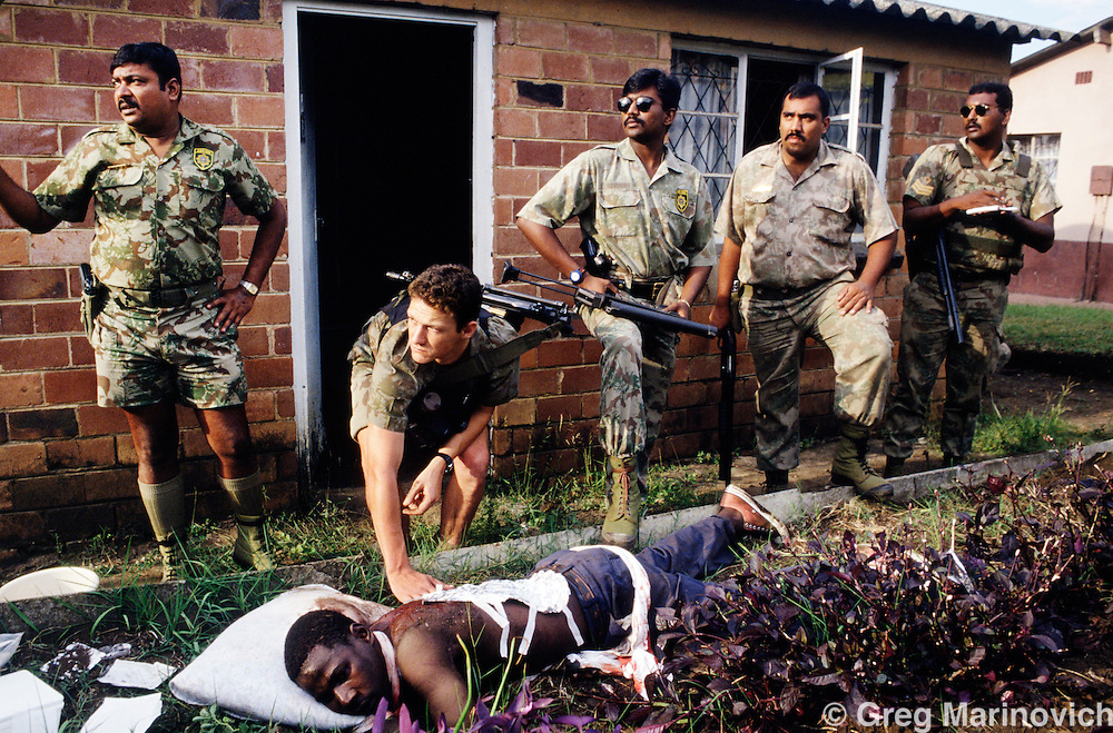 KwaZulu Natal. South Africa. 1994. Riot police treat a man wounded in IFP ANC clashes, KwaMashu,  KwaZulu Natal 1994.