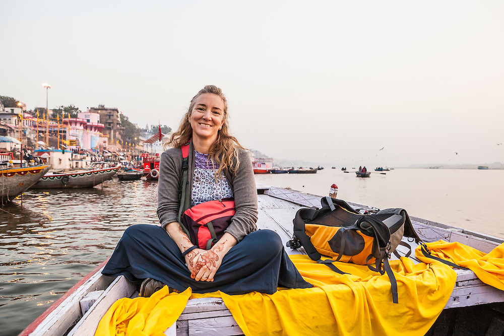 Portrait of a woman tourist riding on a row boat on the Ganges river in Varanasi, India.