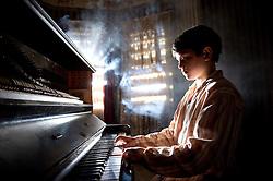 Tom Russell as Young Fish Lamb at piano - Photograph by David Dare Parker