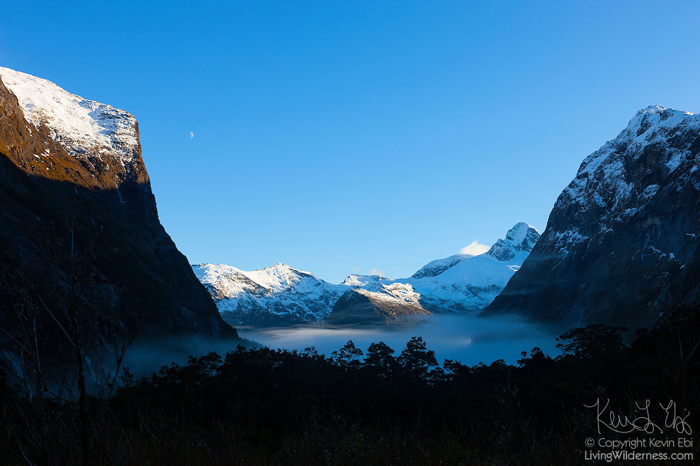 Mount Talbot (left) and Mount Crosscut (right) frame this view of the foggy Gertrude Valley and Darran Mountains in Fiordland National Park, New Zealand. Mount Talbot is 2,105 meters (6,906 feet) tall, and Mount Crosscut has an elevation of 2,203 meters (7,228 feet). The two primary summits in the ridge that stretches across the center of the frame are Barrier Knob, a 1,879-meter-tall (6,165-foot) summit on the left; and Barrier Peak, a 2,039-meter (6,690-foot) summit on the right. Located on the southwestern portion of the South Island, Fiordland National Park is New Zealand's largest national park.