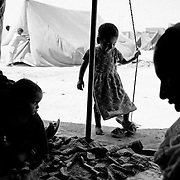 Mehmooda (Hamida's youngest child) is trying on grown-up slippers while Hamida talks to neighbours visiting their tent for a talk. Most children have no toys and there is hardly any schooling for the children living in the camps. Language often is the biggest problem. Most families in the camps speak Sindhi whilst the classes are held in Urdu. Karachi, Pakistan, 2010