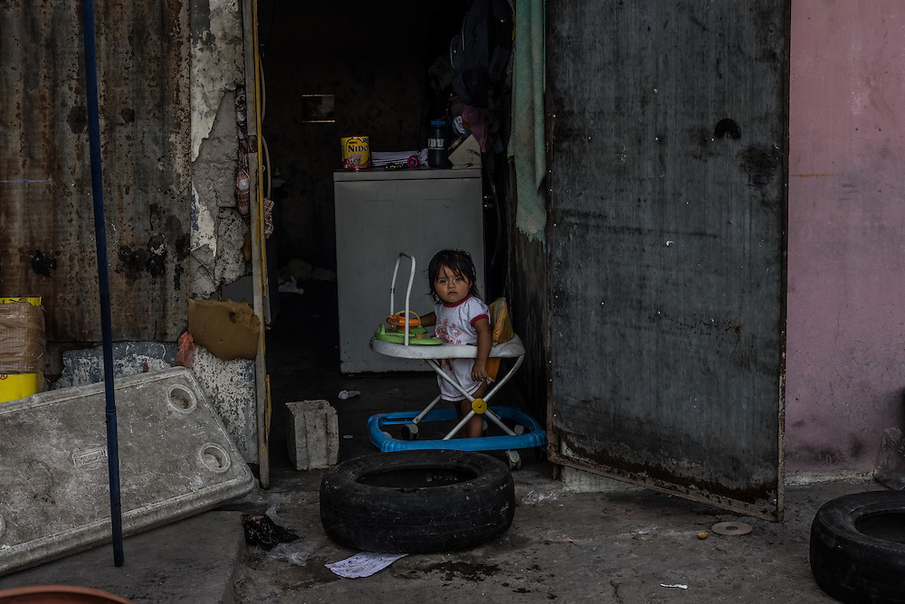 SAN SALVADOR, EL SALVADOR - MAY 25, 2015:  Sophia Alejandra Ramirez, 10 months, plays at home alone with her 10-year-old sister, while her parents work. The government argues that the gang crackdown is just part of a broader strategy to invest in education and job creation in the most violent communities, rehabilitate gang members, and strengthen the rule of law.  The strategy's road map is an ambitious $2.1 billion plan developed with the help of the private sector, churches and aid groups.  But El Salvador's limping economy cannot create the jobs that are needed to provide an alternative to the gangs.  Growth has hovered around 2 percent for years. Remittances from Salvadorans working in the United States account for about 17 percent of national income and half the workforce toils in the informal economy.  PHOTO: Meridith Kohut for The New York Times