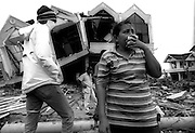 A family returns to the rubble that was previously their home in the Tsunami devastated city of Banda Aceh. January 2005.