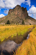 Comanche Point reflects in Comanche Creek as autumn begins to take hold of New Mexico's Valle Vidal.