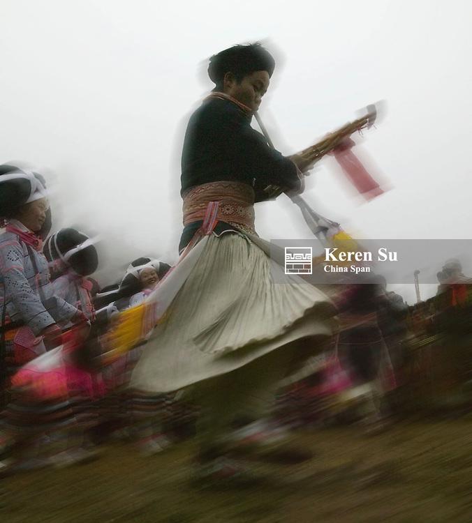 Long Horn Miao people dance and blowing Sheng, bamboo musical instrument, at Flower Dance Festival, Suoga, Guizhou, China