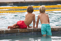 two little boys in a public swimming pool looking out