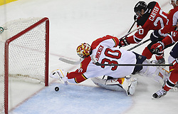 April 24, 2012; Newark, NJ, USA; Florida Panthers goalie Scott Clemmensen (30) covers the puck while New Jersey Devils center Ryan Carter (20) looks for the rebound during the second period of game six of the 2012 Eastern Conference quarterfinals at the Prudential Center.