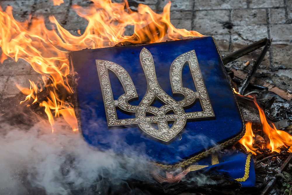 An emblem representing freedom, a national symbol of Ukraine, is burned after being taken from the regional prosecutor's office after the building was stormed by protesters on Thursday, May 1, 2014 in Donetsk, Ukraine.