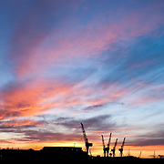 Sunset in spring over the industrial part of Glasgow, Scotland, with a silhouetted skyline of cranes framing the moving clouds.