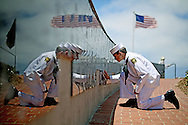 Sea Cadet Andrew Culp,13, cleans a war memorial during a Memorial Day ceremony at the Mount Soledad Veteran's Memorial in La Jolla, CA on Monday, May 27, 2013.  The ceremony honored Glen A. Doherty and Trone Woods, who were Navy Seals and were killed during the attacks on the U.S. Diplomatic Compound in Benghazi last year.(AP Photo/Sandy Huffaker)
