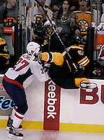 Boston, MA - Boston Bruins defenseman Andrew McQuaid is pushed into the video booth by Washington Capitals defenseman Karl Alzner in the second period at TD Garden on December 18, 2010.   Photo by Matthew Healey