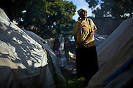 Resident Mary Wanjiru stands near her tent at a Red Cross-run camp in the Mathare section of Nairobi, May 25, 2008. More than 300,000 Kenyans were left homeless after President Mwai Kibaki's disputed re-election in December triggered ethnic clashes, killings and looting. Some aid workers estimate that half of them have returned home, but many are still too afraid or don't have enough resources to do so despite reassurances from the power-sharing government.
