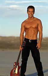 shirtless musician holding an electric guitar outdoors
