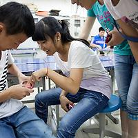 BEIJING, JULY,12-14,2013 : Teilnehmer eines Foto Workshops in der CAOCHANGDI MITTELSCHULE arbeiten mit ihren Kameras im Klassenraum, in der Schule und nach dem Unterricht.