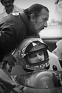 Niki Lauda formed a great bond with mechanic Ermanno Cuoghi when he arrived at Ferrari in 1974: together they won the 1975 World Driver&rsquo;s Championship and missed another title in 1976 to James Hunt by one point due to Lauda's near-fatal Nurburgring accident. <br /> <br /> Here, in 1977, Cuoghi hovers over Lauda on the morning of Lauda&rsquo;s winning his second Driver&rsquo;s title. Ferrari had learned that Cuoghi was moving along with Lauda to Brabham the following season, and fired him on the spot. The team only consented to allow Cuoghi to remain in the pit lane with Lauda if he turned his red Ferrari team jacket inside-out...symbolically breaking his relationship with Scuderia Ferrari. <br /> <br /> Once his second title was in hand, Lauda then declined to race the two remaining Grands Prix, in protest over Ferrari team politics and the humiliation of his good friend. <br /> <br /> And with that, the door opened at Ferrari for Gilles Villeneuve.