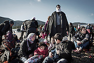 Arrived on the shores of Lesbos near Mytilene airport, refugees from Afghanistan and Syria wait to be shuttled to a registration camp by bus, Greece on 08 January, 2016. Lesbos, the Greek vacation island in the Aegean Sea between Turkey and Greece, faces massive refugee flows from the Middle East countries.