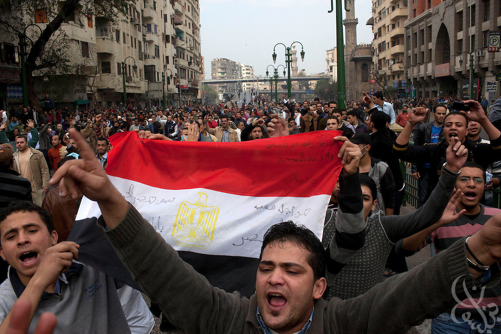 Egyptian protesters carry an egyptian flag down Port Said street during massive and unprecedented demonstrations January 28, 2011 across Cairo, Egypt . The protests, inspired by the recent revolution in Tunisia, have struck a chord with Egypt's population, tired of inflation, high unemployment and alleged corruption within the Mubarak government..Slug: Egypt.Credit: Scott Nelson for the New York Times