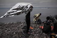 Before heading to a transit camp, refugees from Afghanistan check their belonging after they landed by rubber boats on the shores of Lesbos near Skala Sikaminias, Greece on 02 January, 2016. Lesbos, the Greek vacation island in the Aegean Sea between Turkey and Greece, faces massive refugee flows from the Middle East countries.