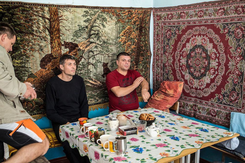 DNIPRODZERZHINSK, UKRAINE - OCTOBER 11: Ruslan, Sergiy Nebaba, and Oleksandr, a pastor from Khartsyzk (L-R), gather for coffee and tea in a makeshift kitchen at the sports school where they live with about 60 other displaced people from Eastern Ukraine on October 11, 2014 in Dniprodzerzhinsk, Ukraine. The United Nations has registered more than 360,000 people who have been forced to leave their homes due to fighting in the East, though the true number is believed to be much higher.(Photo by Brendan Hoffman/Getty Images) *** Local Caption ***