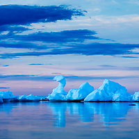 Canada, Manitoba, Churchill, Blue icebergs reflected in still water on Hudson Bay at dusk on summer evening