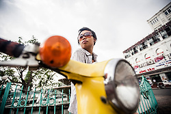 Portrait of a young vietnamese woman leaning on her motorbike, Hanoi, Vietnam, Southeast Asia