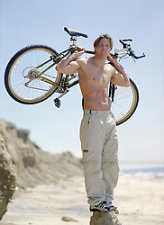 shirtless man holding a bicycle over his shoulders at the beach