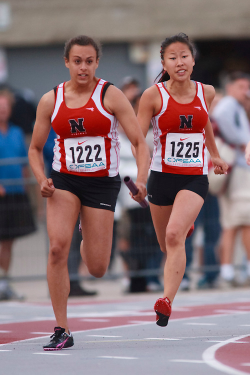 (London, Ontario}---09 June 2010) Jess Bonnema of Northern  (Sarnia)  receives the baton from Leanne Holdaway during the 4 X 100 meter relay heats at the 2010 OFSAA Ontario High School Track and Field Championships. Photograph copyright GEOFF ROBINS / Mundo Sport Images, 2010.